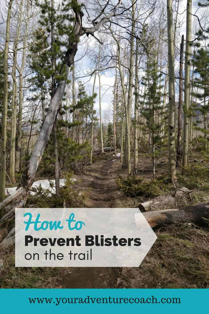 how to prevent blisters on the trail picturing a hiking trail with tall trees