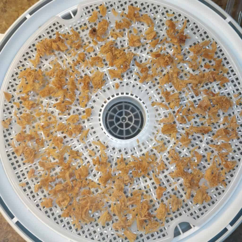 dried chicken on a dehydrator tray